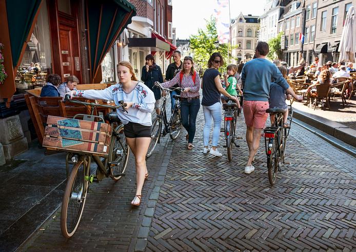 Fietsers lopen met fiets aan de hand over de Vismarkt.