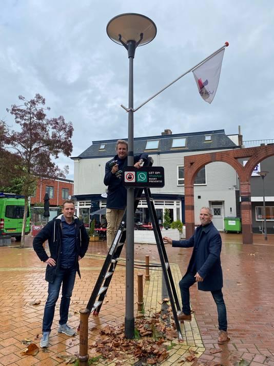 Wethouder Ronald Haverkamp en de bestuursleden Frank Martens (rechts) en Roy Koenhen hangen een buurtpreventiebord op in de Overtuin in Velp.