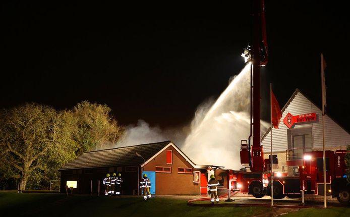 De brandweer blust het vuur op sportpark BZC Brakel, waar de kleedkamers in vlammen opgingen.