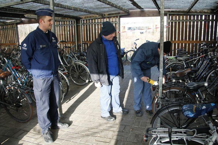 Medewerkers van het Fietspunt slepen de fietssloten onder politietoezicht open.