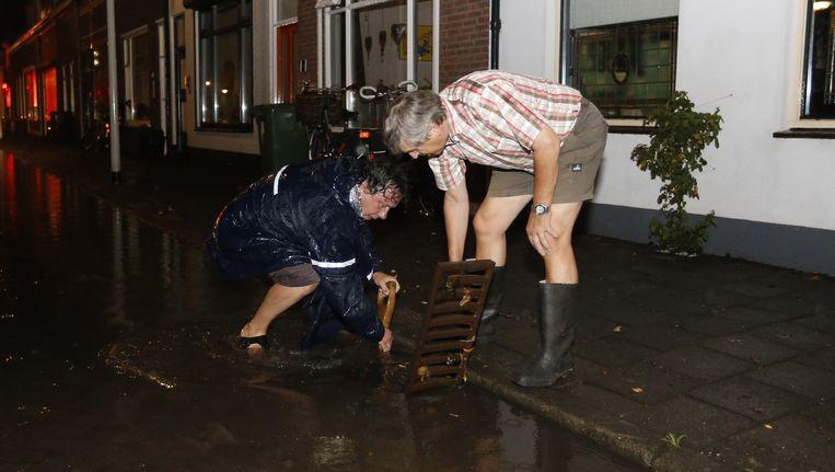 Bewoners proberen een put open te krijgen na noodweer in Bergen op Zoom. Het regen- en onweersgebied dat Nederland vanuit het zuiden binnentrok zorgde op verschillende plaatsen voor overlast. Beeld anp