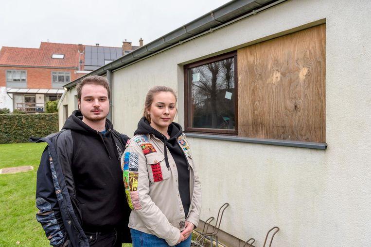 Xander Hubert (20) en Zoë Wieme (20) bij het raam dat met een baksteen werd ingeslagen.