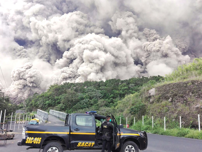 Politieagenten zoeken naar overlevenden van de vulkaan Fuego na een uitbarsting op 3 juni in Guatemala.