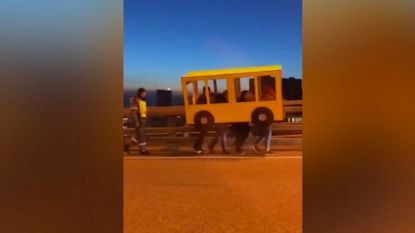 Hilarisch: Mannen verkleden zich als een bus om brug over te steken