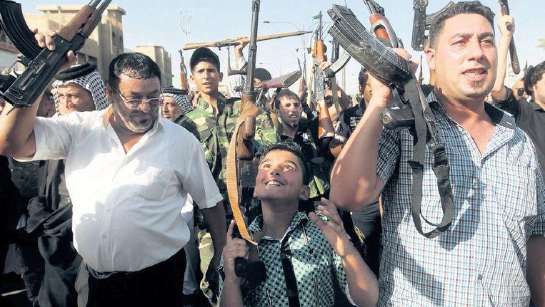 Een Iraakse jongen houdt zijn wapen omhoog tussen burgers die zich hebben aangemeld bij het Iraakse leger om te vechten tegen Isis. Beeld afp