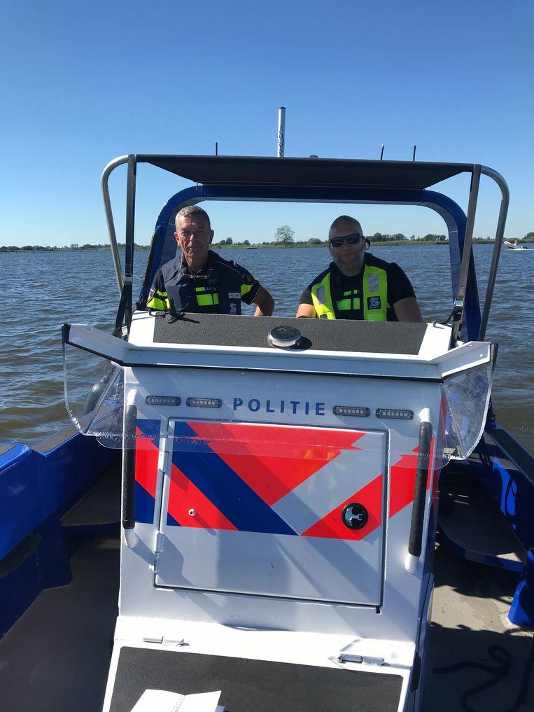 Sibo Dam (links) met een collega aan boord van een politieboot Beeld Kaya Bouma