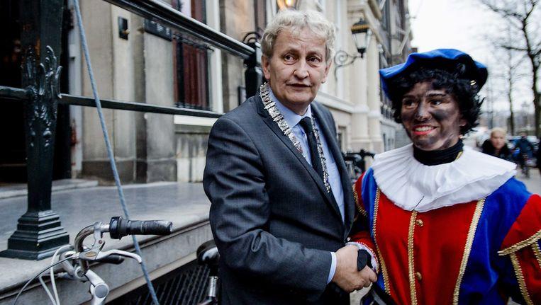 Een roetveegpiet schudt de hand van burgemeester Eberhard van der Laan. Beeld ANP