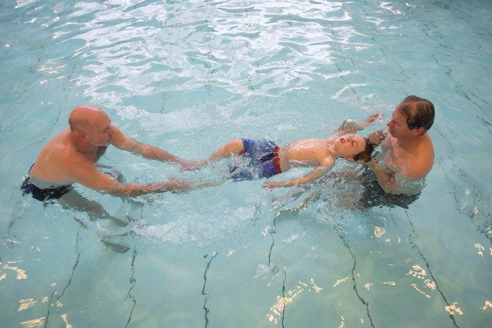 Vrijwilligers Frank Vogels en Harrie van der Meijden helpen de 7-jarige Chris Wijsbek.