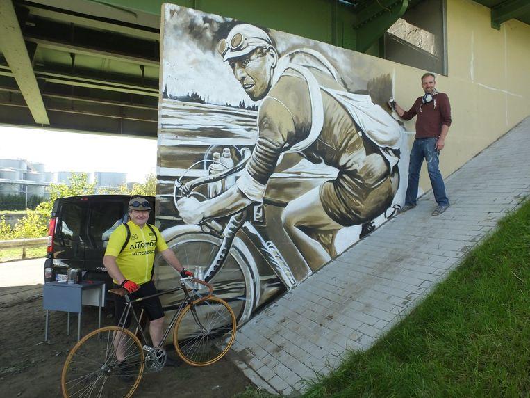 Jesse Van Gompel legt de laatste hand aan het portret va Lucien Buysse. Links op de foto: gemeenteraadslid Lieven Tack die af en toe opduikt als re�ncarnatie van de wielerlegende.