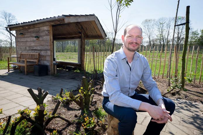 Projectleider Jeroen Kwak van respijthuis Frits, waar mensen aan hun herstel kunnen werken. Op de achtergrond het tuinhuisje dat gasten uit dankbaarheid gebouwd hebben.