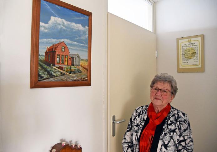 Adrie van Overdulve-de Kraker in de hal van haar appartement in Terneuzen. Links het schilderij van haar ouderlijk huis in de Lovenpolder bij Hoek. Achter haar hangt het certificaat van de Israëlische Yad Vashem-onderscheiding die in 1994 postuum aan haar ouders werd toegekend.
