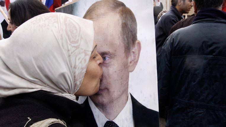 Een Syrische vrouw kust vandaag op straat in Damascus een afbeelding van de nieuwe Russische president. Beeld AP