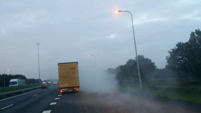Een enorme stofwolk achter de lekkende vrachtwagen.