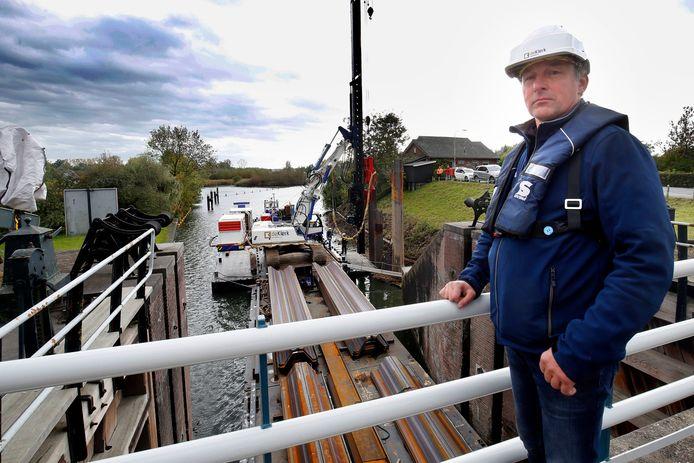 Uitvoerder Mark Teunissen op de Noordersluis in Asperen met op de achtergrond de push-pull damwanddrukker.