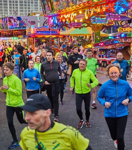 Hardlopers van Rotterdam Running Crew rennen langs de kermisattracties