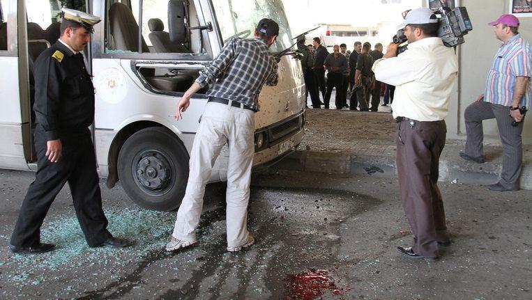 Syrische agenten inspecteren een beschadigde bus na de bombardementen in Damscus. Beeld epa