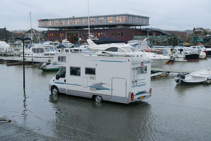 Ook in Sliedrecht staat het water hoog. Een aan de Havenstraat geparkeerde camper staat met de wielen in het water.
