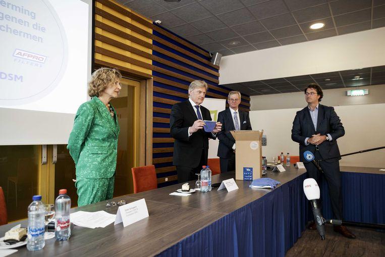 Edith Schippers (links), directeur van DSM overhandigde minister voor medische zorg Martin van Rijn in het Hilversumse Tergooi ziekenhuis de eerste Nederlandse mondkapjes.  Beeld ANP