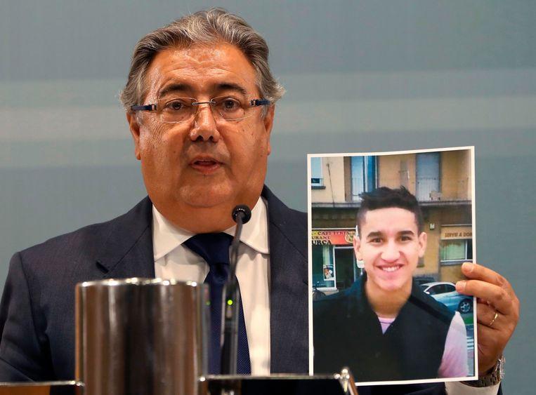 De Spaanse minister van binnenlandse zaken toonde gisteren een foto van de toen nog voortvluchtige terrorist Younes Abouyaaqoub, die in de namiddag werd gepakt en doodgeschoten, zo'n dertig kilometer ten westen van Barcelona. De politie meent dat Abouyaaqoub de bestelbus bestuurde waarmee de aanslag in Barcelona werd gepleegd. Beeld EPA