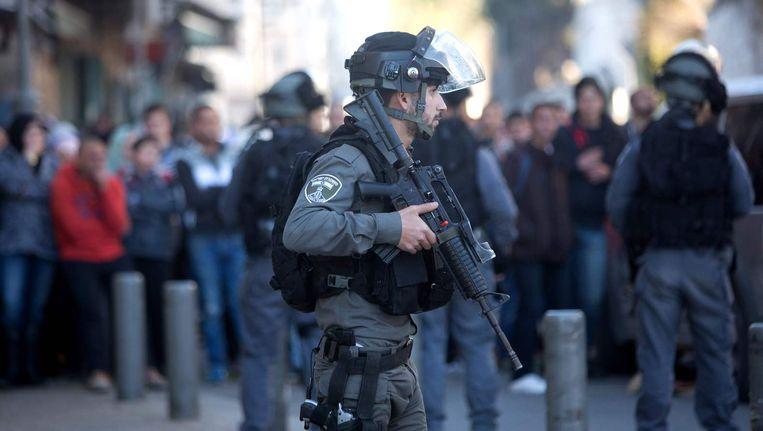 Een Israëlische agent staat bij de plek waar woensdag drie Palestijnen werden doodgeschoten. Beeld afp