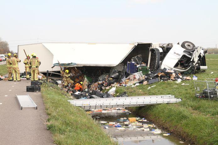 De inhoud van de vrachtwagen ligt grotendeels in de sloot.
