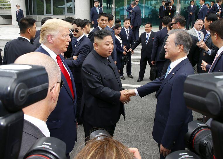 De Noord-Koreaanse leider Kim Jong-un en de Zuid-Koreaanse president Moon Jae-in onder toeziend oog van de Amerikaanse president Donald Trump. Beeld EPA