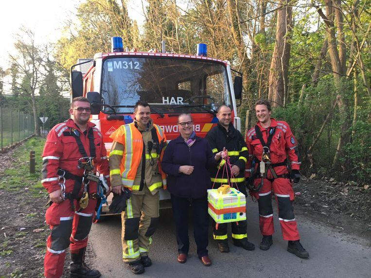 De reddingswerkers van de brandweer met de vierkante doos.