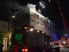 Flat onbewoonbaar door brand; brandweerlieden zetten hoogwerker in