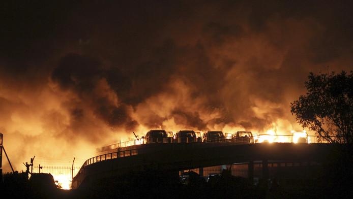 Voertuigen staan in brand na de explosie op een industrieterrein in Tianjin, China.