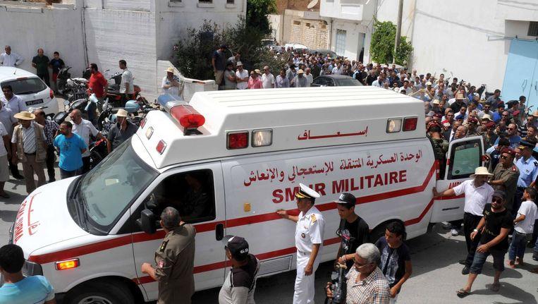 Een ambulance draagt de kist met het lichaam van een militair arts uit Tunesië die bij de aanslag van dinsdag om het leven kwam. Beeld afp