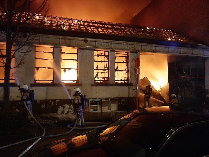 Brandweermannen proberen het vuur te doven in een opslagplaats aan de Rafaelstraat in de Brusselse gemeente Anderlecht.