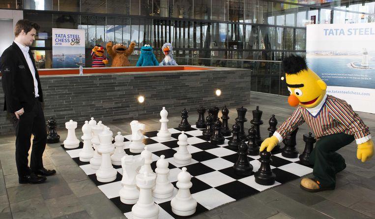 Bert, enthousiast aangemoedigd door Ernie, Tommie, Elmo en Pino, speelt een partijtje schaak tegen wereldkampioen Magnus Carlsen. De vijfde ronde van het Tata Steel-schaaktoernooi werd gisteren gespeeld in Hilversum.  Beeld ANP