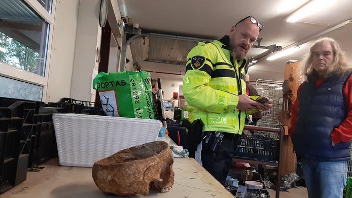 De wijkagent van Twello informeert bij medewerker Boy Denekamp van Kringloop Twello over de door hem aangetroffen menselijke schedel.