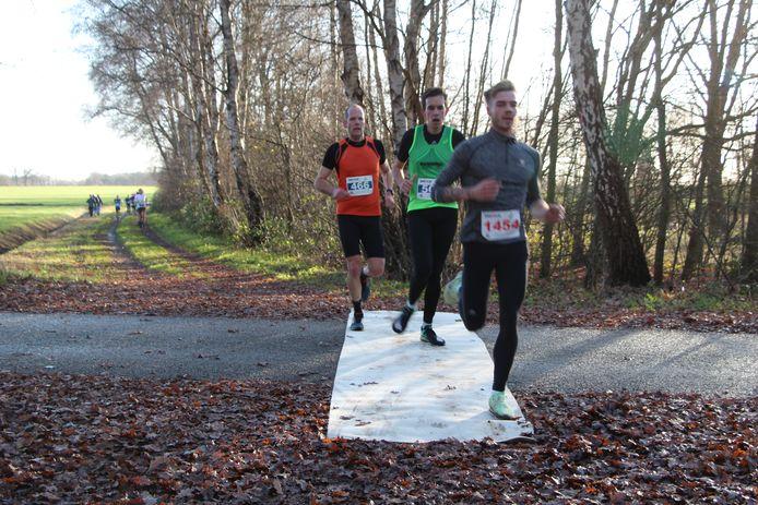 Deelnemers aan de 10 km-cross kruisen de Rietmolenseweg vanaf de Mallumse Es.