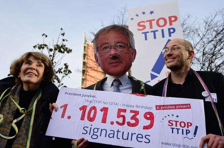 Demonstranten tegen TTIP dragen op 9 december 2014 in Brussel het gezicht mee van Jean-Claude Juncker, voorzitter van de Europese Commissie. Beeld Emmanuel Dunand / AFP