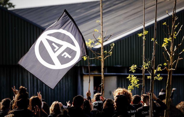 De actievoerders zwaaien met een vlag van het Animal Liberation Front (ALF).