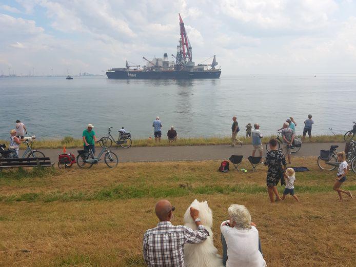 Belangstellenden kijken op de dijk bij Ritthem naar het grootste werkschip ter wereld.