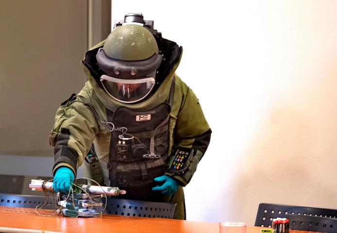 Een aspirant explosievenopruimer maakt een 'bom' onschadelijk in het gemeentehuis van Gemert.