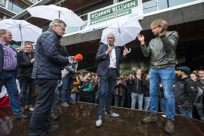 Demonstrerende boeren juichen bij het provinciehuis van Overijssel als de verantwoordelijke gedeputeerde Gert Harm ten Bolscher van Landbouw (links) bekend maakt de stikstofregels in te trekken.