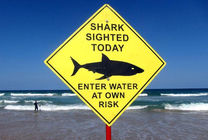 Een bord op een Australisch strand waarschuwt zwemmers en surfers voor de aanwezigheid van haaien.