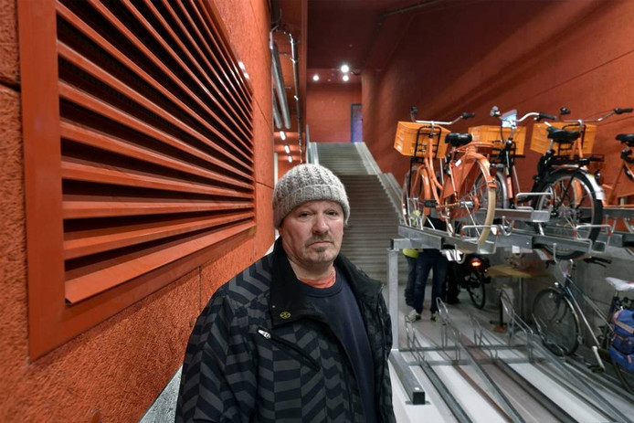 Henk Saat bij de roosters die koude lucht blazen in de fietsenkelder onder Rozet blazen.