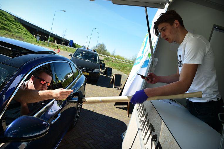 Aspergeteler Corné Ooms reikt een van zijn klanten een bestelling aan, in zijn drive-thru in Hoogerheide. De klant moet afrekenen met de pin. Beeld Marcel van den Bergh