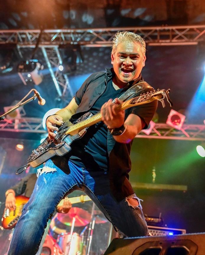 Albert Rumengan op het podium met zijn gitaar.