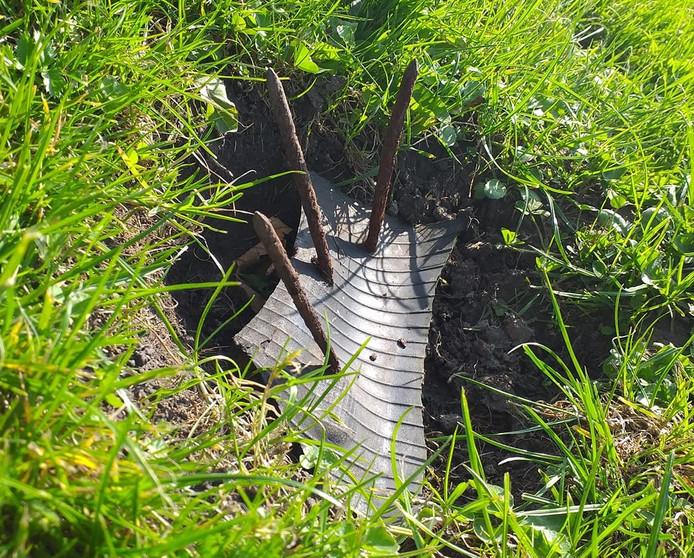 De val is gemaakt van een stuk rubber, waaraan meerdere grote spijkers bevestigd zijn. De val was ingegraven in het gras.