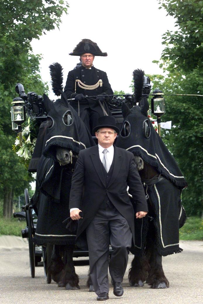 Harry Klijmij zoals veel mensen in Zaltbommel hem kennen, lopend voor een rouwstoet uit. In dit geval voor een koets met paarden.