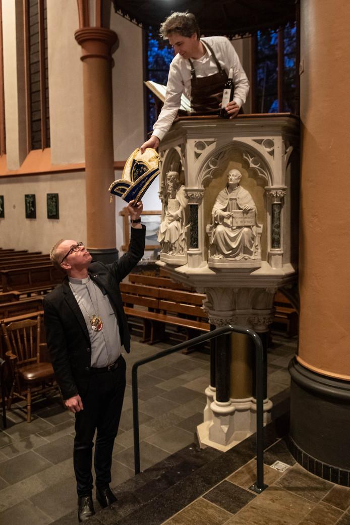 Pastoor Casper Pikkemaat overhandigt de carnavalssteek aan kroegbaas Ruud Droste, die alvast plaats heeft genomen op de preekstoel.