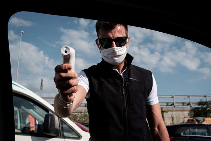 Een medewerker neemt de temperatuur op van toeristen die met de ferry naar het Italiaanse eiland Sardinië willen.