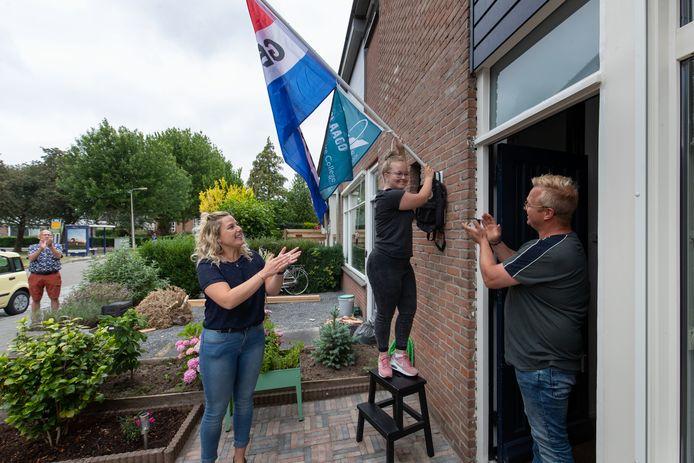 Marit Slik (16) hangt de vlag uit, ze is geslaagd! Biologiedocente Lieke Zweers brengt, samen met haar collega's van het Almere College VIA vandaag een verrassingsbezoekje aan de geslaagde leerlingen.
