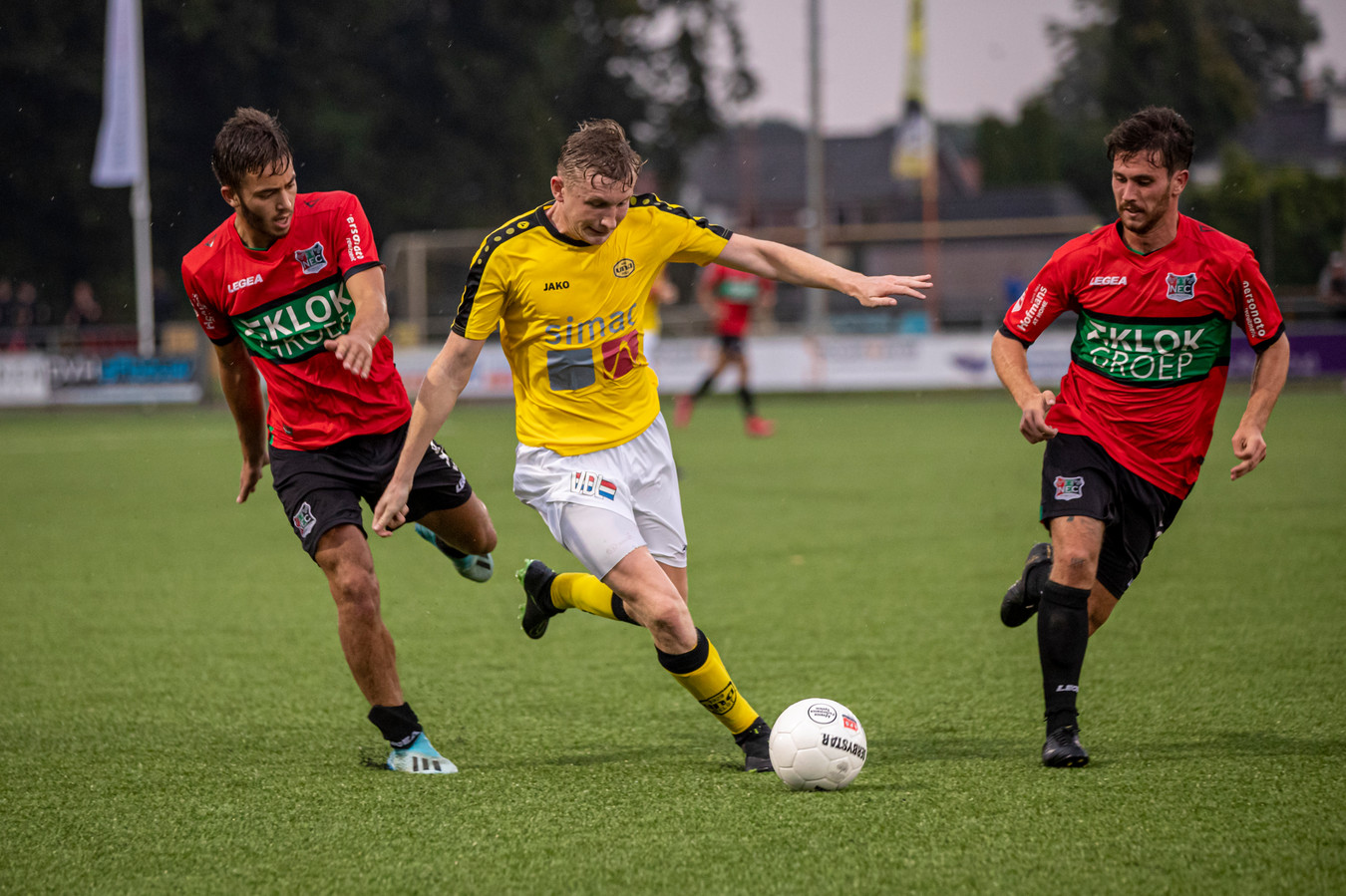 Noël van Gerven van UNA baant zich een weg tussen twee spelers van NEC.