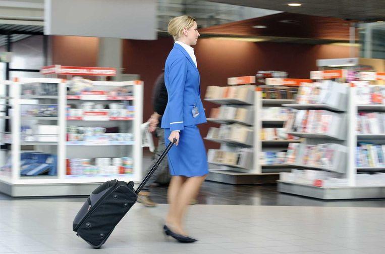 KLM-stewardess op Schiphol. Het schrappen van het aantal managementlagen is een trend bij grote bedrijven. Beeld anp